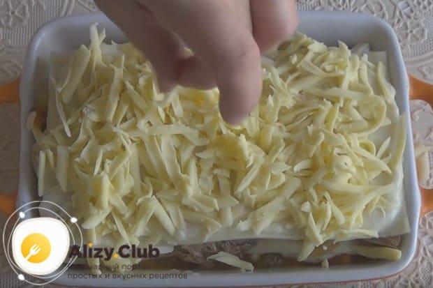 Покрываем листы теста оставшимся соусом и посыпаем сыром, а затем отправляем блюдо в духовку.
