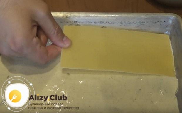 Смазав дно формы для выпечки соусом, кладем листы лазаньи.