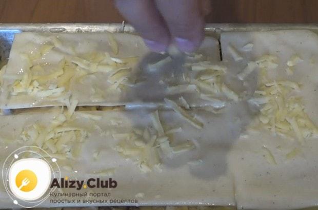 Выложив последний слой теста, покрываем его соусом бешамель и посыпаем сыром.