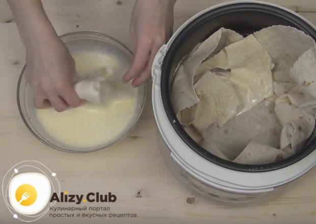 Рвем лаваш на кусочки, смачиваем их в приготовленном соусе и укладываем в мультиварку.