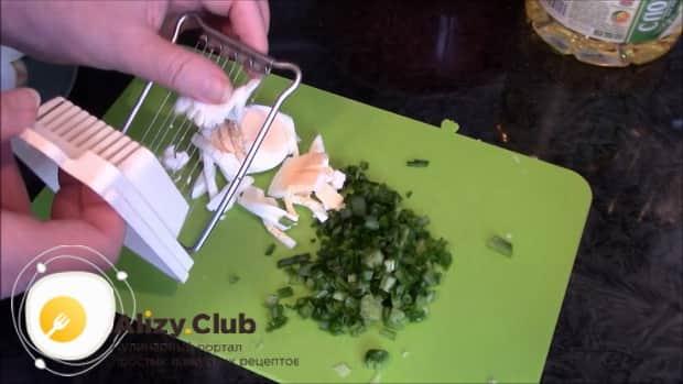 Перед тем как приготовь очень ленивые пирожки с луком и яйцом, нарежьте ингредиенты.