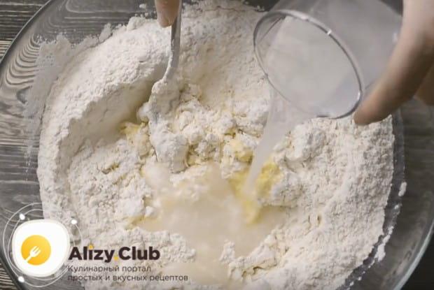 Частями вводим воду в муку и начинаем замешивать тесто.
