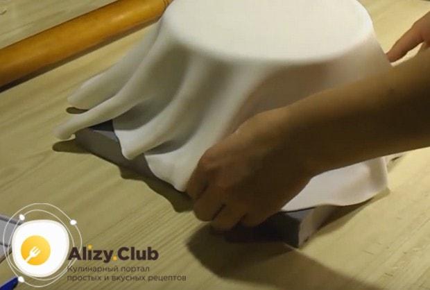 Аккуратно при помощи скалки переносим мастику на выравнянный торт.
