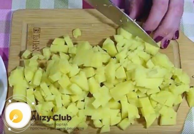 Отваренный в мундире картофель очищаем и тоже режем кубиком.