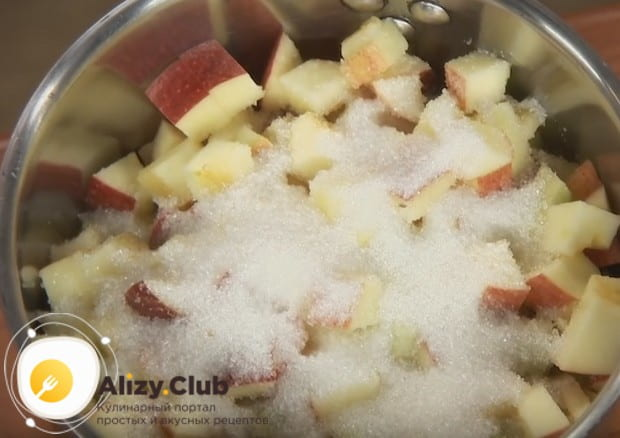 Часть яблок ржем кубиками и отправляем в кастрюлю к бруснике, засыпав их сахаром.