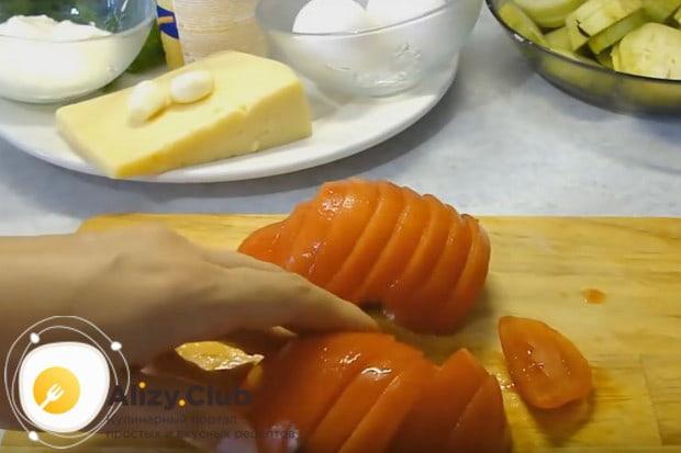 Нарезаем очищенный помидор тонкими полукольцами.