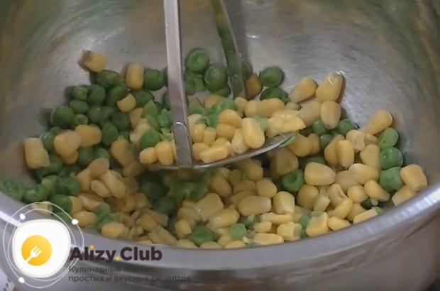 Слегка отваренные кукурузу и горошек немного разминаем толкушкой, но не пюрируем.