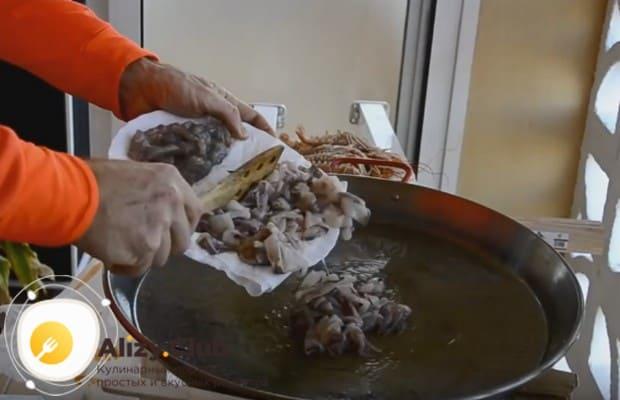 Теперь выкладываем на сковородку кальмары, нарезанные кольцами.