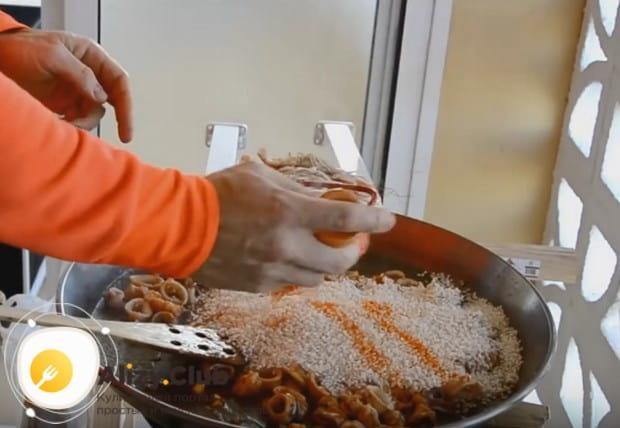 Теперь высыпаем на сковороду рис, добавляем шафран, а также оранжевый пищевой краситель.
