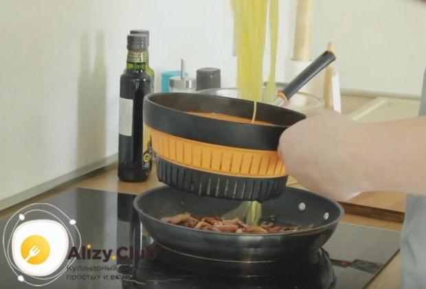 Готовые спагетти перекладываем на сковороду к бекону с луком.