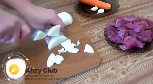 Для приготовления перловой каша с мясом, нарежьте лук.
