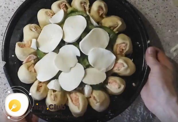 Украсив пирог болгарским перцем и каперсами, выкладываем на него кусочки сыра моцарелла.