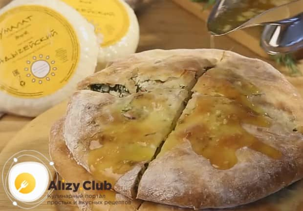 Готовый пирог с сыром и зеленью поливаем растопленным сливочным маслом.