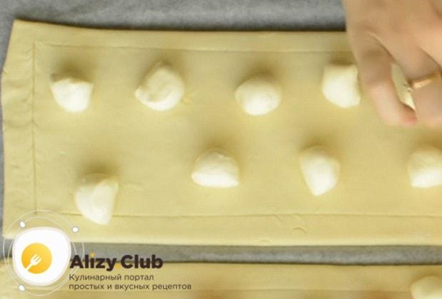 По всей поверхности теста, кроме краев, раскладываем кусочки моцареллы.