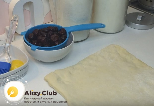 Чтобы приготовить пирог из слоеного теста с замороженной вишней, надо предварительно разморозить ягоды и откинуть их на дуршлаг.