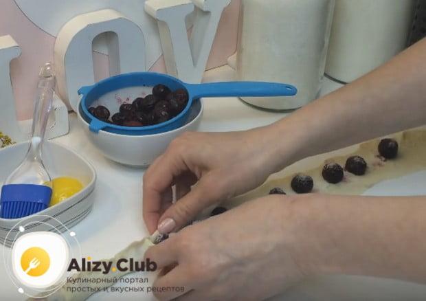 Посыпаем вишни сахаром и тщательно пощипываем края теста так, чтобы шов был сверху.