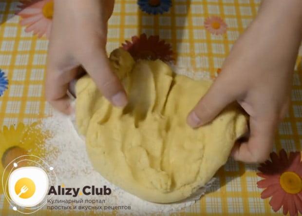 Выкладываем тесто на припыленный мукой стол и делаем из него лепешку.