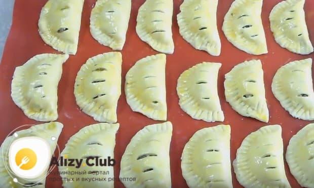 Выкладываем пирожки на противень и смазываем их взбитым желтком или яйцом.
