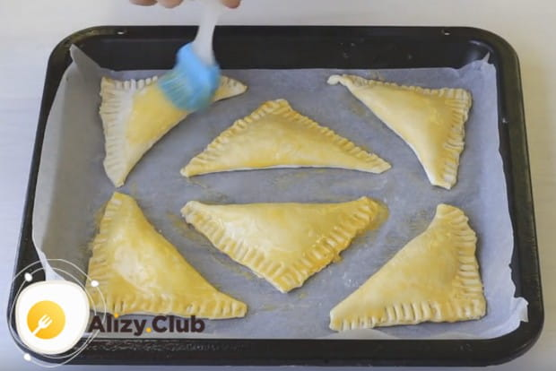 Перед отправкой в духовку смажем пирожки желтком.