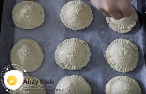 Смазываем пирожки белком и посыпаем кунжутом.