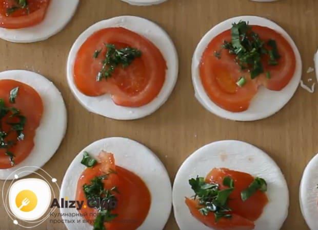 на каждую заготовку из теста кладем кружочек помидора и присыпаем его зеленью.