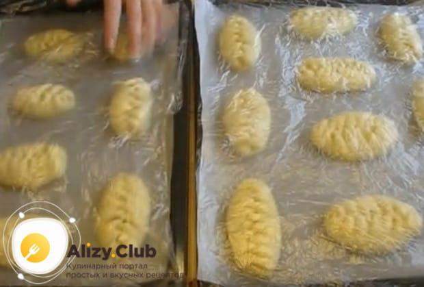 Ставим пирожки с повидлом из дрожжевого теста на расстойку, накрыв их пленкой.