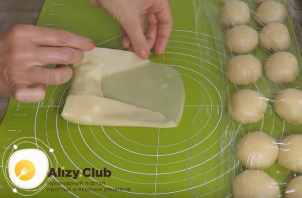 Аккуратно заворачиваем начинку в тесто, стараясь не порвать его.