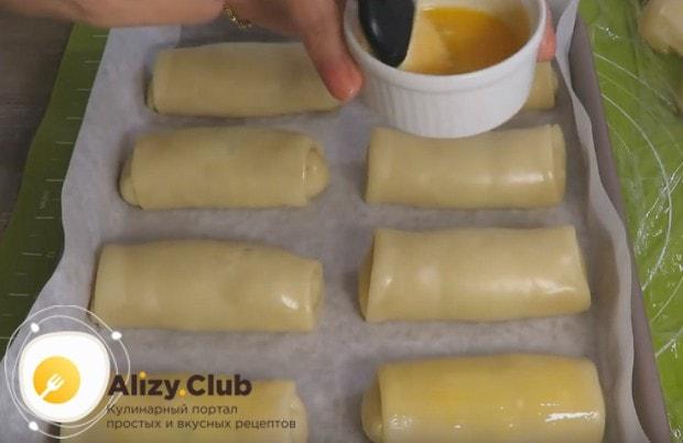 Укладываем подготовленные пирожки на противень и смазываем из желтком.