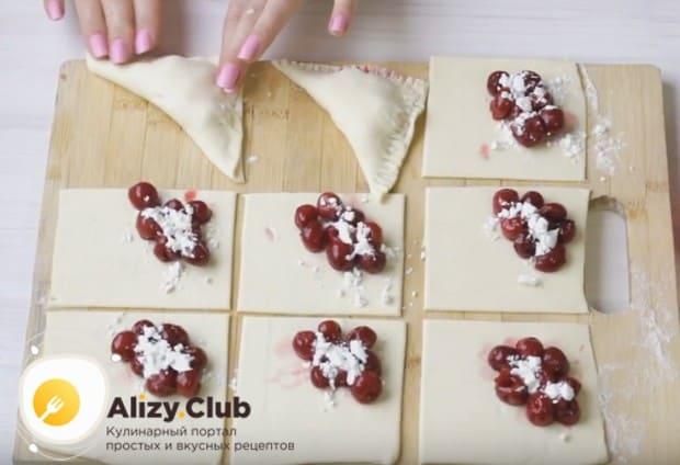 накрываем начинку свободной половинкой теста и формируем треугольные слоеные пирожки с вишней.