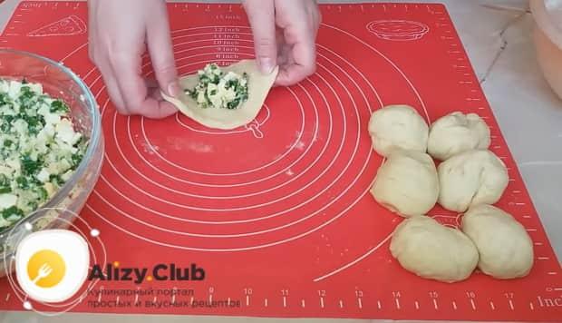 Перед тем как сделать пирожки с луком и яйцом,положите начинку на тесто.