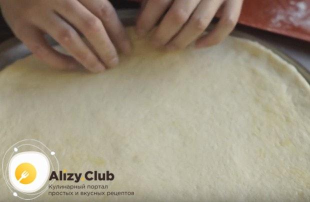 Выкладываем тесто в круглую форму для пиццы и разравниваем.