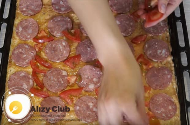 На колбасу кладем кусочки помидора.