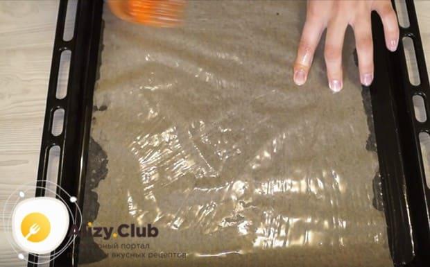 На противень кладем лист пергамента и смазываем его растительным маслом.