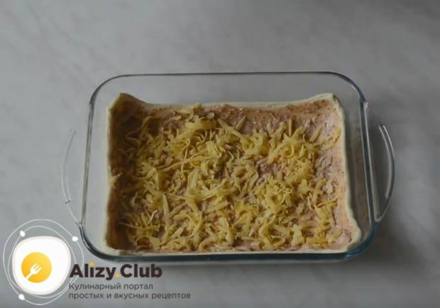 Посыпьте заготовку частью натертого сыра.