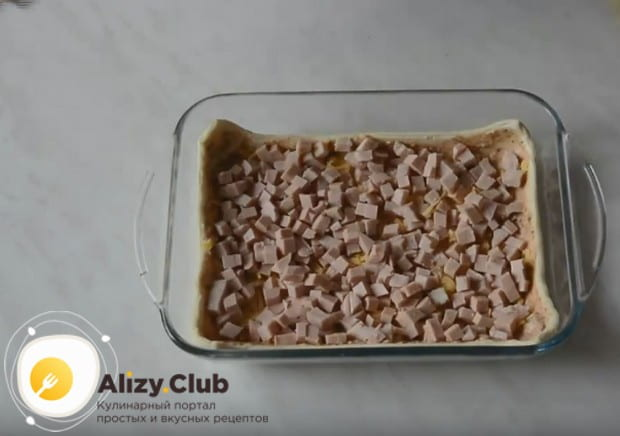 Выложите на сыр слой нарезанной кубиком колбасы.