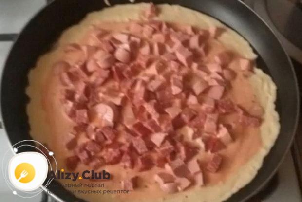 Для приготовления пиццы на сковороде, нарежьте колбасу.