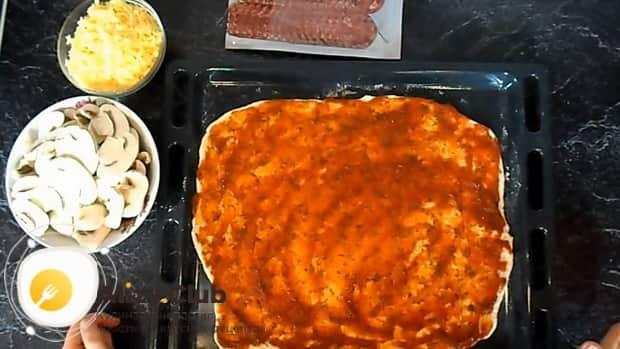 Выложите начинку для пиццы с колбасой на соус.