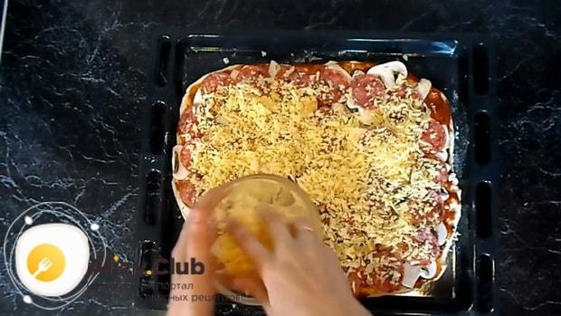 Посыпьте начинка для пиццы с колбасой сыром.