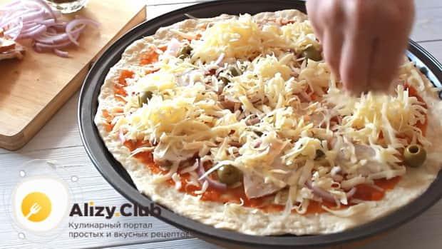Для приготовления пиццы с курицей выложите начинку на тесто.