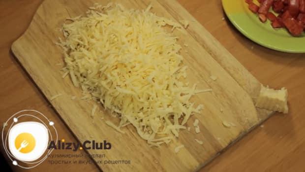 Натрите сыр для приготовления пиццы с копченой колбасой