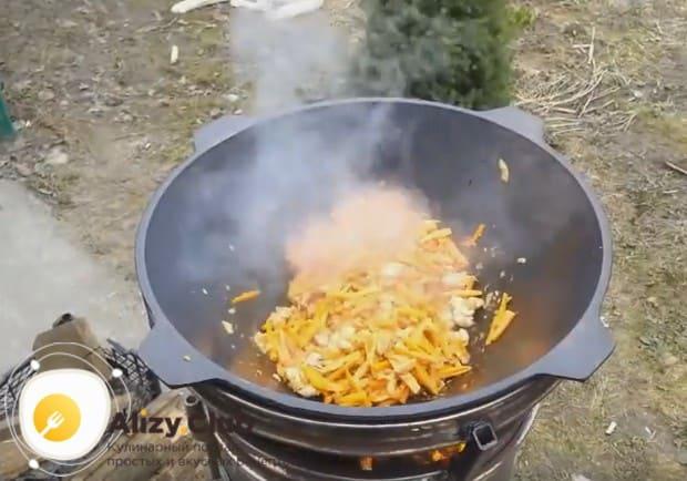 После мяса добавляем в казан морковь, нарезанную соломкой.