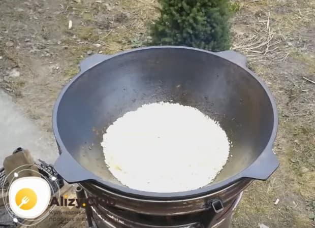 Выкладываем на мясо с овощами рис, не перемешивая компоненты между собой.