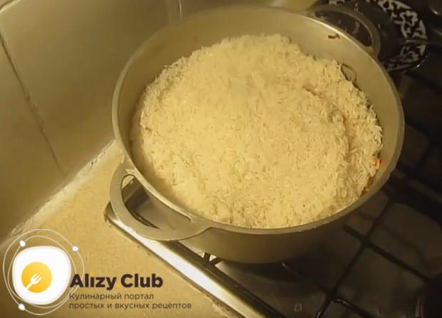 Выкладываем и равномерно распределяем рис сплошным слоем поверх моркови.