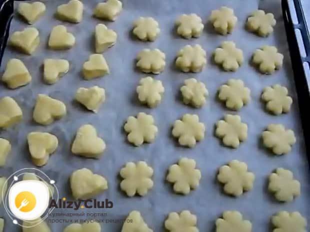 По рецепту, для приготовления печенья на огуречном рассоле, выложите заготовки на противень.