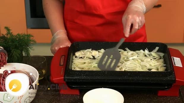 Для приготовления бифштекса из свинины, нарежьте лук.