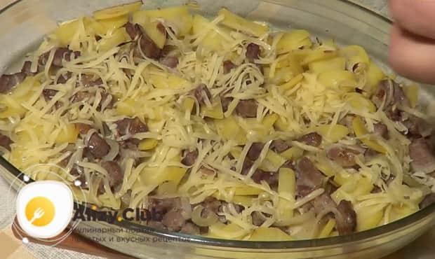 Посыпьте картошку с мясом сыром и запеките в духовке