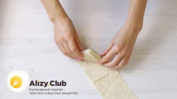 Для приготовления лаваша с сыром на сковороде сверните заготовку.
