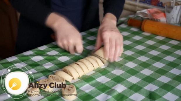 Для приготовления печенья с корицей разрежьте рулет пополам.
