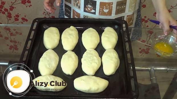 Для приготовления пирожков с рисом и яйцом в духовке, выложите заготовки на противень.