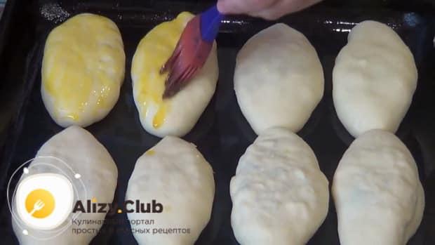 Для приготовления пирожков с рисом и яйцом в духовке, смажьте заготовки яйцом.
